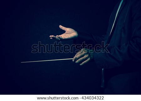 Orchestra conductor hands, Musician director holding stick on dark background