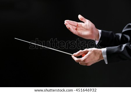 Orchestra conductor hands on black background - stock photo