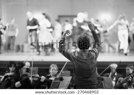 Orchestra conductor leading the musicians in the theater - stock photo