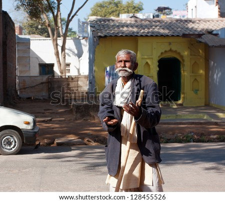 ORCHHA, INDIA - DEC 20: Emotional senior man talks on the sunny street on December 20 2012 in Orchha, Madhya Pradesh, India.  60-plus age group in India will increase to 100 million people in 2013. - stock photo