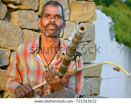Orchha, India - Dec 17, 2014: Old Indian temple musician with jheeka (rectangular Indian tambourine) playing his instrument and singing at Ram Raja Mandir on Dec 17, 2014