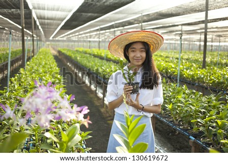 orchid and girl, Young Asian girl wearing weave hat in orchid farm - stock photo