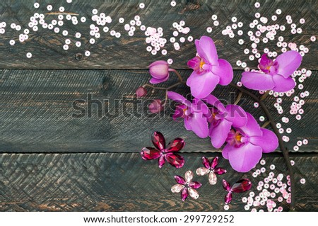 Orchid flower, crystals and sequins on the old wooden background. view from above - stock photo