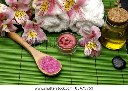 Orchid with herbal salt in spoon with zen stone and massage oil set for spa - stock photo