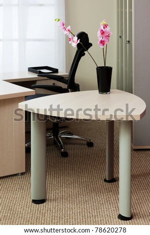 orchids on the table in a modern office - stock photo