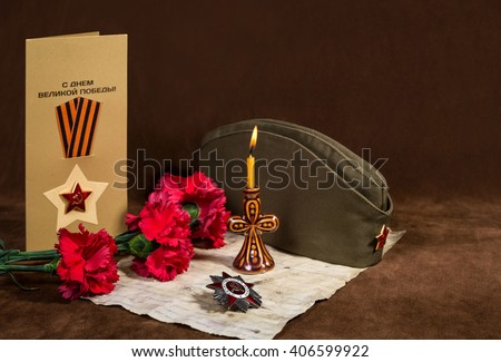 Order of the Patriotic War 1st class, three red carnations, letter from the Front, greeting card, forage-cap and a candle on a brown background - stock photo