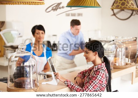 Ordering or paying by digital tablet in a cafe - stock photo