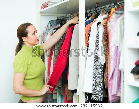 Orderly woman arranging clothes at wardrobe indoor - stock photo