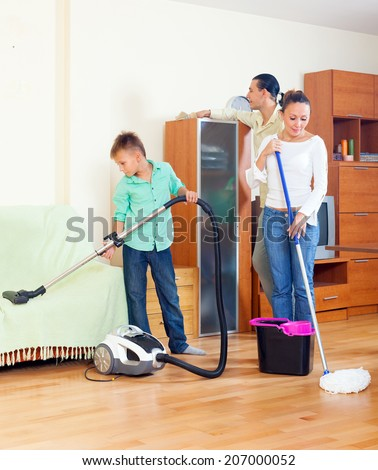 Ordinary family doing  cleaning with  cleaning equipment in living room