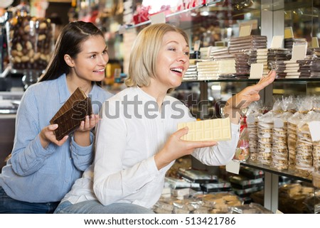 Ordinary female customers choosing delicious milk chocolate in shelf