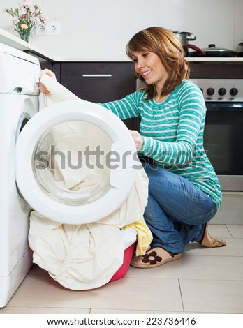 Ordinary girl in green using washing machine at home - stock photo