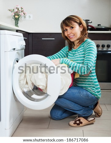 Ordinary housewife in green using washing machine at home
