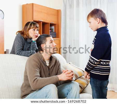ordinary parents berating teenager son at home - stock photo