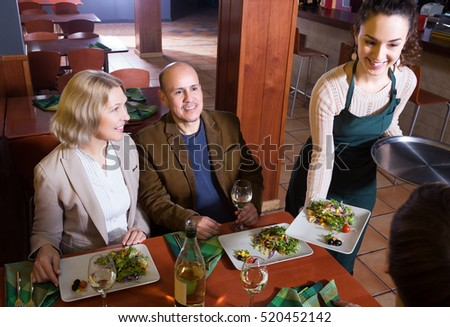 Ordinary senior couple enjoying food and wine in restaurant