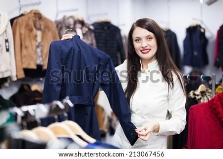 Ordinary woman choosing jacket at clothing boutique - stock photo