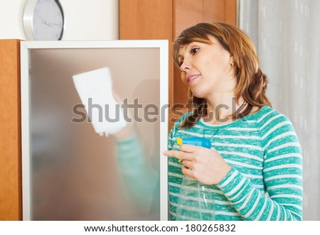 Ordinary woman in green dusting glass of furniture at home