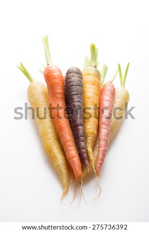 organic and fresh carrots in different colors, isolated on white, close up, vertical - stock photo