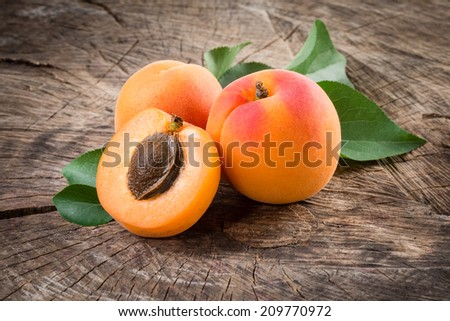 Organic apricots with leaves on wooden background - stock photo