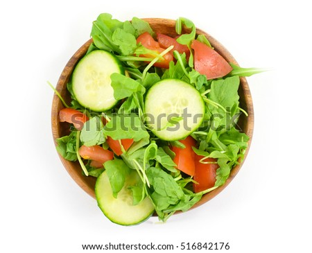 Organic arugula salad with tomato and cucumber slices on wood plate - isolated