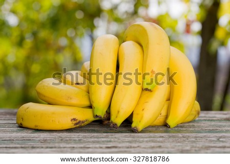 organic bananas on the wooden table at the farm, outdoor - stock photo