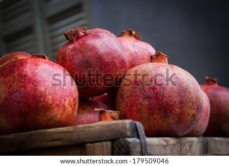 Organic bio pomegranate fruits in wooden boxes at the farmers market. Pomegranate is one of Rosh Hashana (Jewish New Year) symbols. Still life. Closeup. Selective focus. - stock photo