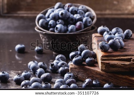Organic blueberries served in a black vintage bowl and rustic wooden board with vintage cup and metal bucket with a scoop on a background
