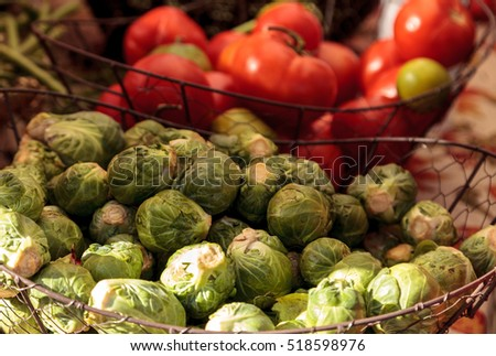 Organic Brussels sprouts and tomatoes grown on a farm and displayed at a farmers market