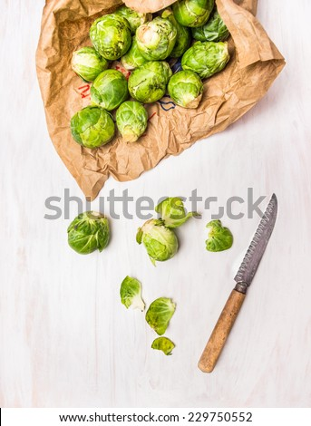 Organic Brussels sprouts Peeling with knife on white wooden background - stock photo