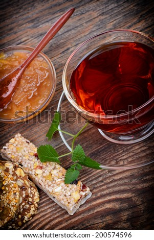 Organic cereal biscuits on a plate and tea on wooden background