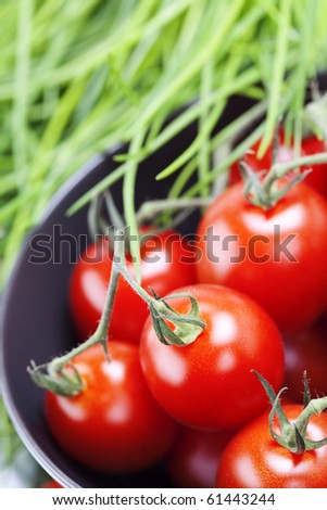 organic cherry tomatoes and A bunch of fresh chives  on old green plate - stock photo