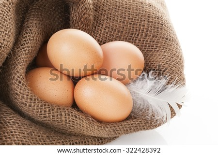 Organic chicken eggs in burlap bag isolated on white background.
