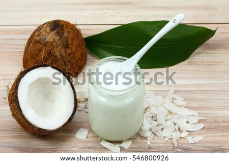 Organic coconut oil from coconuts in a white glass jar, fresh coconut cut in half and its pieces