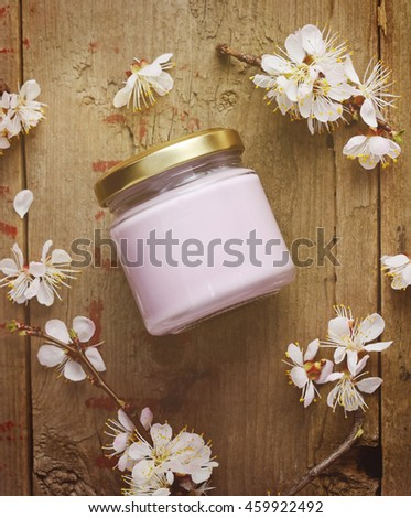 Organic cosmetic cream with apricot tree flowers on a wooden background. Vintage spa still life. Top view