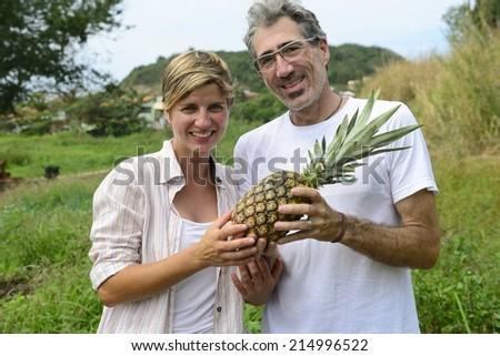 Organic farming: Farmer couple showing a pineapple - stock photo