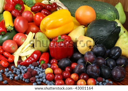 Organic food products. Autumn harvest - ripe vegetables and fruits. Tomatoes, beans, plums, pepper, raspberries, zucchini, pears and other food. - stock photo