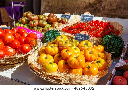 Organic fresh different tomatoes from mediterranean farmers market. Healthy local food market. Variety of tomatoes: green, red, yellow, black. Market in Gordes, Provence, France. - stock photo