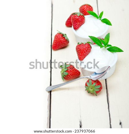 organic Greek yogurt and strawberry over white rustic wood table - stock photo