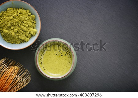 Organic Green Matcha Tea in a small cup with bamboo whisk, top view - stock photo