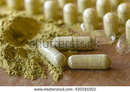 Organic Herbal drug an alternative medicine with hand capsule packing - stock photo