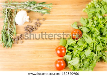Organic Herbs and vegetables lying on aw wooden board - stock photo