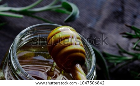 Organic honey falling off wooden drip with sage and rosemary herbs is background