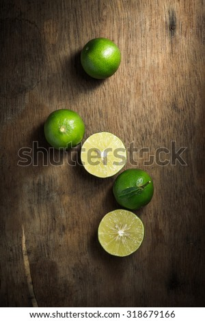 Organic lime on rustic wood board background, Still life photography with lime on wood board background, The art of food photography with limes on rustic wood board background - stock photo