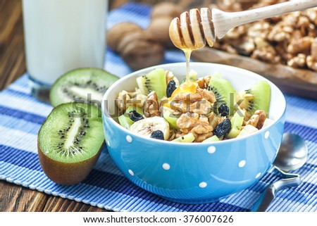 Organic oatmeal porridge in ceramic bowl with bananas, honey, walnuts, kiwi fruit and raisins. Healthy breakfast - health and diet concept on the wooden table, close up