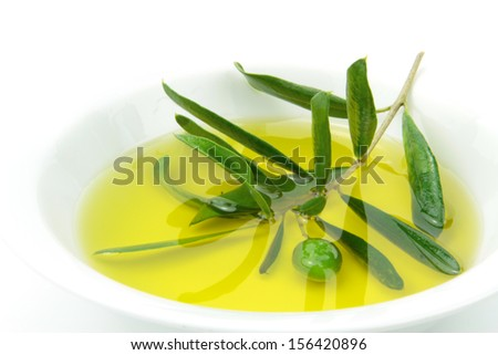 Organic olive oil and green olive branch in bowl. - stock photo