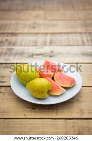 Organic pink guava on wood background - stock photo