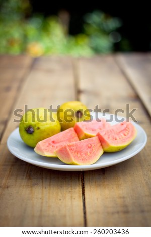 Organic pink guava on wooden table in garden - stock photo