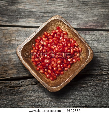 Organic pomegranate seeds on a rustic wooden board - stock photo