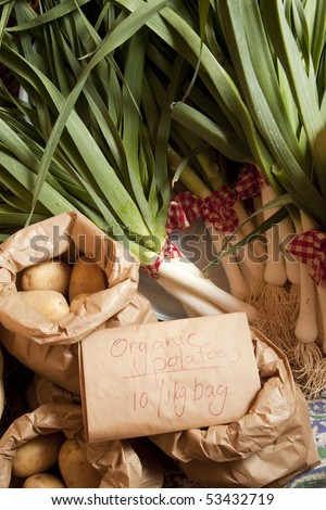 Organic potatoes and leeks on sale at a market with a sign and paper bags in foreground.