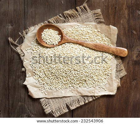 Organic quinoa with a spoon on a wooden table - stock photo