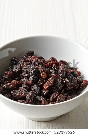 Organic raisins in white bowl on white wooden table background